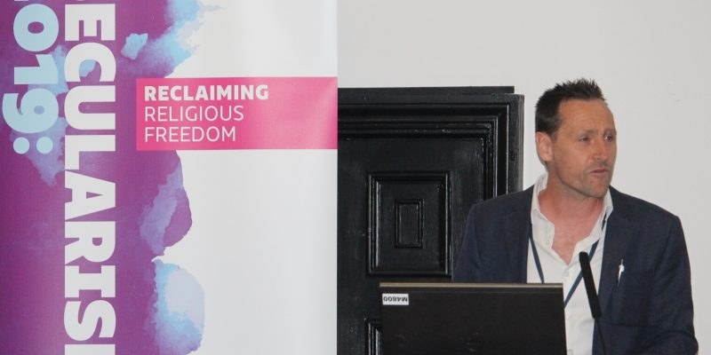 Stephen Evans in front of Secularism 2019 banner